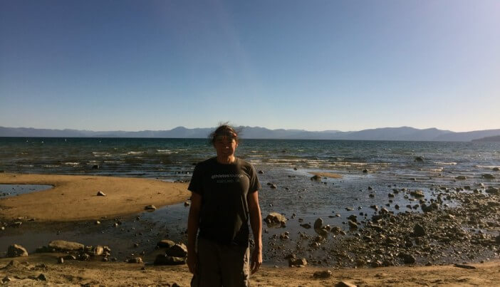 DJ standing in front of a low Lake Tahoe